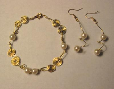 Golden swirls coupled with pearls and matching earrings.